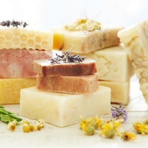 Stacks of homemade organic bars of soap with lavender and calendula flowers